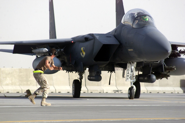 US Air Force (USAF) AIRMAN First Class (A1C) William Gilmer, a F-15E Strike Eagle aircraft Crew CHIEF, assigned to the 379th Expeditionary Maintenance Squadron (EMXS), taxies out his aircraft for a mission armed with GBU-12 Pave II 500-pound Laser Guided Bombs, AMI-9 Sidewinder Missiles and AIM-120 Advanced Medium Range Air-to-air Missiles, at a forward deployed location in Southwest Asia, during Operation ENDURING FREEDOM