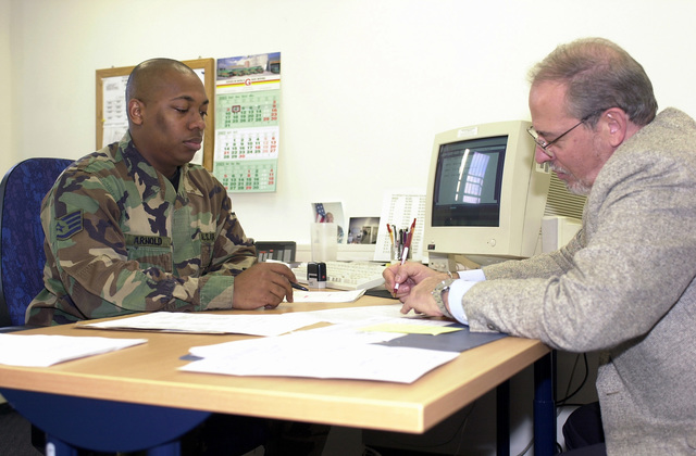 US Air Force (USAF) STAFF Sergeant (SSGT) Darryl Arnold Jr., Non-Commissioned Officer in Charge (NCOIC) of Customer Service, and Counseling, assist Mr. Roger Alvernaz, Deputy Commander, 52nd Services Squadron (SVS), with the necessary paperwork for household goods pick-up, inside the Traffic Management Office at Spangdahlem Air Base (AB), Germany