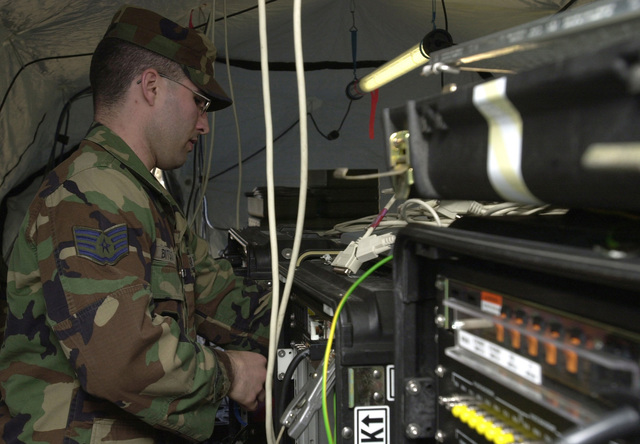 US Air Force (USAF) STAFF Sergeant (SSGT) Michael Bitson, Non-Commissioned Officer In Charge (NCOIC) of Network Management, installs a cryptography machine at Mihail Kogalniceanu Air Base, Romania, during Operation ENDURING FREEDOM