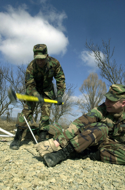 US Air Force (USAF) Technical Sergeant (TSGT) Reginald Hall (left), and STAFF Sergeant (SSGT) Dan Vorlander, both Satellite Communications Technicians, assigned to the 458th Air Expeditionary Group (AEG), Communication Squadron (CS), drive an antenna anchor into the ground at Mihail Kogalniceanu Air Base, Romania, during Operation ENDURING FREEDOM