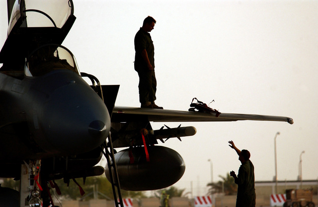 A US Air Force (USAF) maintenance member tosses up a safety lock for the USAF F-15C Eagle aircraft canopy hydraulic lift to another maintenance member. The lock will keep the canopy up in case of hydraulic pressure drop while the maintenance member in working in the cockpit. The Eagle is armed with AIM-120C Advanced Medium Range Air-to-Air Missiles (AMRAAM), and a 370-gallon pod hangs on the wing pylon