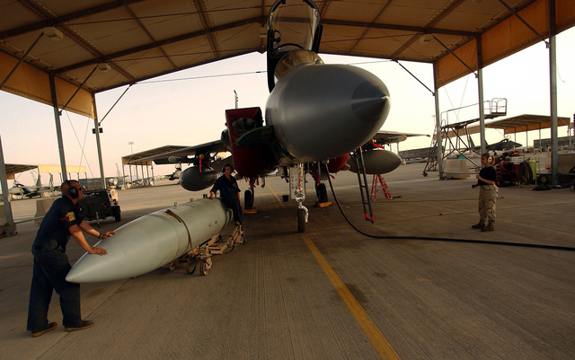 US Air Force (USAF) members, deployed to the 363rd Expeditionary Aircraft Maintenance Squadron (EAMS), prepare to attach a 600-gallon external fuel pod to a USAF F-15C Eagle aircraft, 67th Fighter Squadron (FS), Kadena Air Base (AB), Japan, prior to a mission at a forward deployed location in Southwest Asia. The Eagle is armed with AIM-120C Advanced Medium Range Air-to-Air Missiles (AMRAAM)