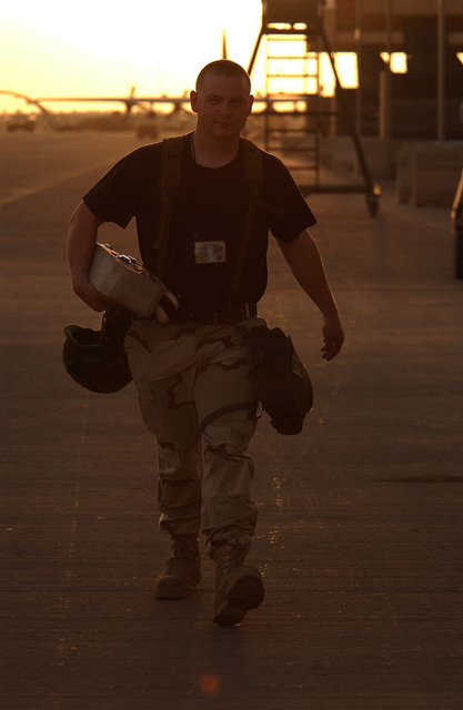 US Air Force (USAF) STAFF Sergeant (SSGT) Charles Beers, Weapons Load CHIEF, 363rd Expeditionary Aircraft Maintenance Squadron (EAMS), carries his gas masks and Kevlar helmet while working on the flightline at a forward deployed location in Southwest Asia during Operation ENDURING FREEDOM