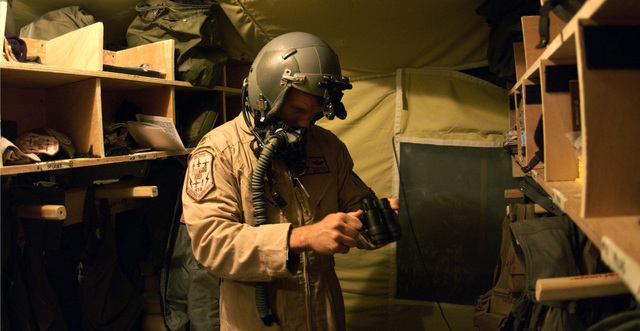 A US Air Force (USAF) Major (MAJ), an F-16 Fighting Falcon pilot, assigned to the 410th Air Expeditionary Wing (AEW), prepares his night vision goggles before a mission at a forward deployed location during Operation IRAQI FREEDOM