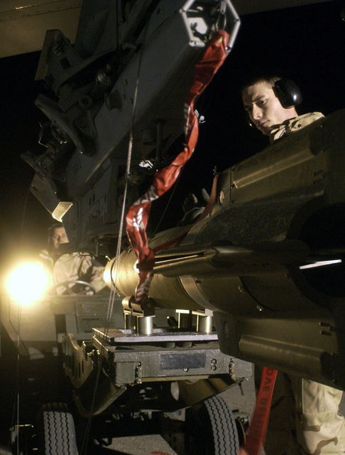 US Air Force (USAF) munitions personnel assigned to the 410th Air Expeditionary Wing (AEW) at a forward deployed location use an MJ-1B Munitions Loader as they fix a GBU-12 Paveway II to an USAF F-16 Fighting Falcon. The guidance system is not yet attached to the munitions. The 410th AEW prepare the aircraft for take off for sorties on A-Day, the commencement of the air war for Operation IRAQI FREEDOM, at a forward location