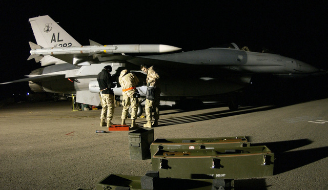 US Air Force (USAF) munitions personnel assigned to the 410th Air Expeditionary Wing (AEW) at a forward deployed location work on guided munitions on the pylon of an USAF F-16 Fighting Falcon. The Falcon has an AIM-120A Advanced Medium Air-to-Air Missile (AMRAAM) a fixed to the wing tip. The 410th AEW prepare the aircraft for take off for sorties on A-Day, the commencement of the air war for Operation IRAQI FREEDOM, at a forward location
