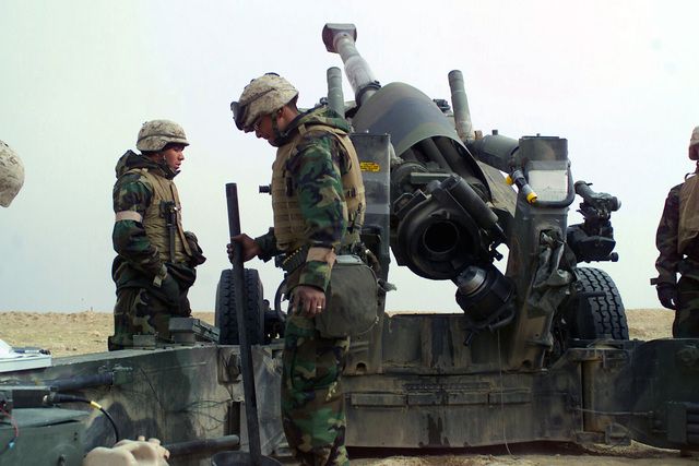 US Marine Corps (USMC) Corporal (CPL) Robert Jimenez, from New Braunfels, Texas, with Lima Battery, 3/1, prepares to swab the barrel of an M198 Towed Field Howitzer, in support of Operation ENDURING FREEDOM