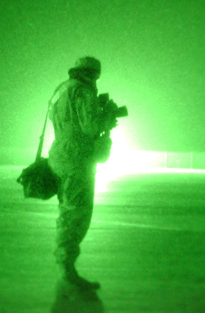 A nightscope view as US Air Force (USAF) AIRMAN (AMN) Bridget Rapp, Photographer, 384th Expeditionary Communications Squadron (ECS), Visual Information (VI), prepares to document a night aircraft launch during Operation ENDURING FREEDOM