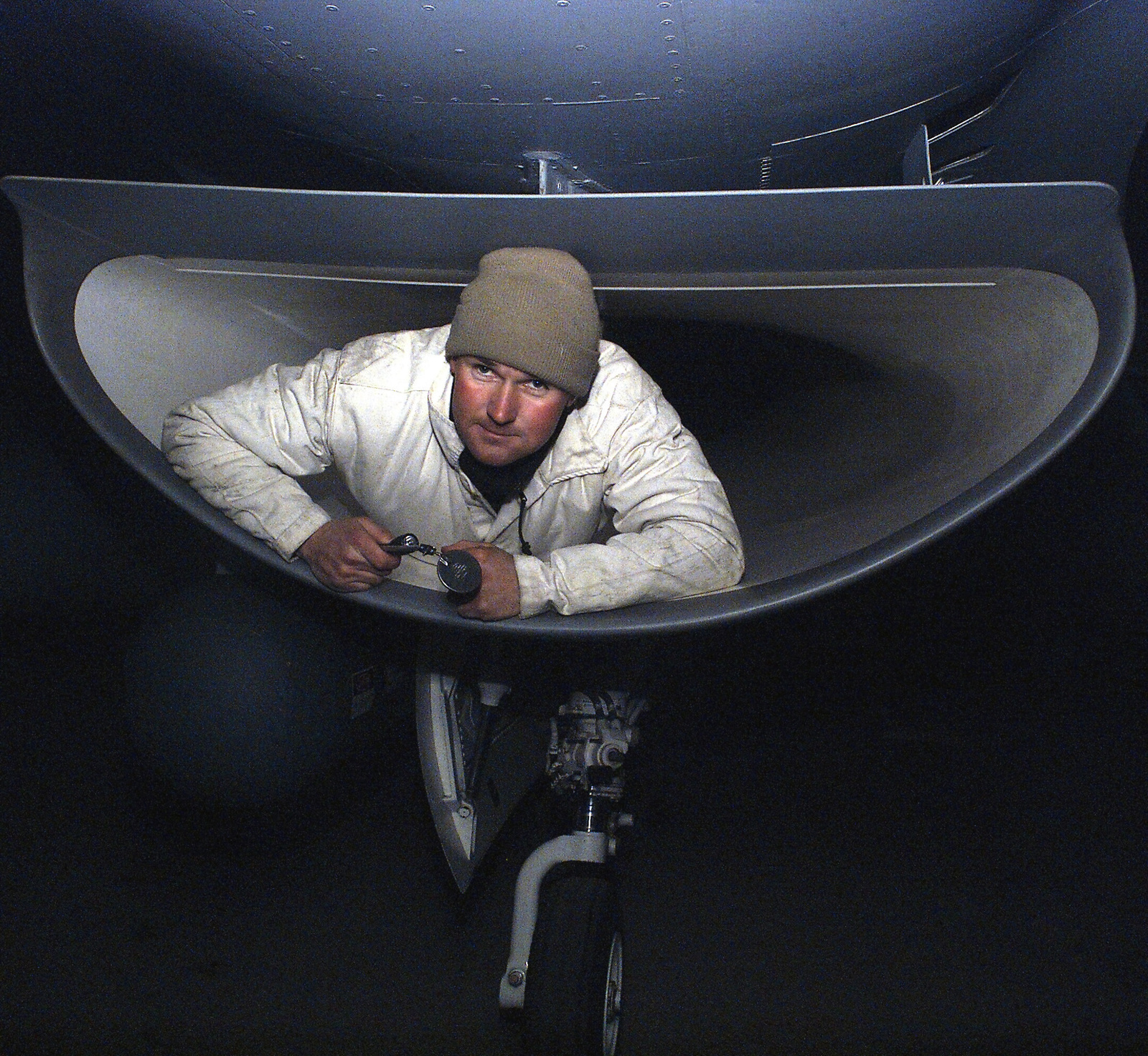 A US Air Force (USAF) 410th Air Expeditionary Wing (AEW) maintenance member surfaces from the inside of the F-16 Fighting Falcon intake after inspecting the fan blades during Operation ENDURING FREEDOM at a forward deployed location