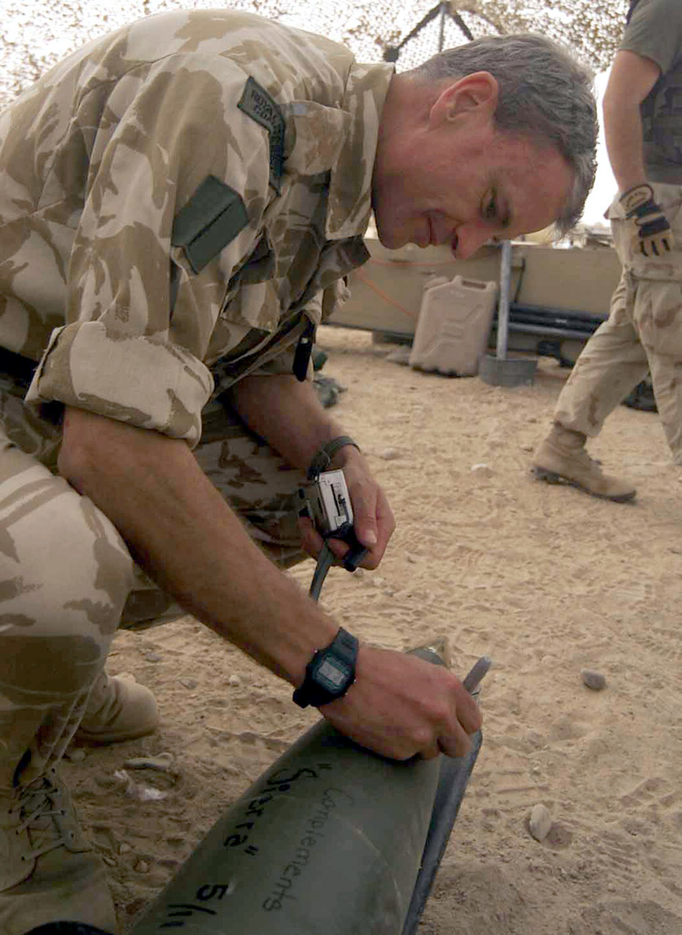 Brigadier General (BGEN) J. B. Dutton and Commanding Officer (CO) of the 3rd Commando Brigade, British Royal Marines (BRM), signs a 155mm howitzer round set to be the first field artillery round fired into Iraq, during Operation IRAQI FREEDOM