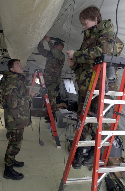 US Air Force (USAF) Major (MAJ) Eric Suescun, a General Surgeon, MAJ Peter R. Little a Surgical Nurse and MAJ Tracy Colby, a Orthopedic Surgeon, all from Landsthul Regional Medical Center, Germany, install lighting at a Mihail Kogalniceanu Air Base (AB), Romania, medical tent, in support of Operation ENDURING FREEDOM