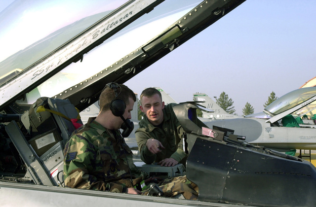 US Air Force (USAF) STAFF Sergeant (SSGT) Daniel Higgins (left), Crewchief, 31st Aircraft Maintenance Squadron (31 AMXS), locates the cause of the error signal that fellow Crewchief USAF AIRMAN First Class (A1C) John Williams registered on the dashboard of the 31st Fighter Wing (FW) F-16 Fighting Falcon cockpit during post-maintenance operations checks