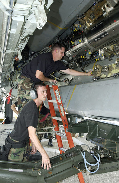 US Air Force (USAF) STAFF Sergeant (SSGT) Landon Favors (foreground) and USAF SSGT Clayton Carver, both Weapons Loaders, assigned to the 2nd Bomb Wing (BW), work to load a Conventional Air Launch Cruz Missile into the weapons bay of a USAF B-52H Stratofortress aircraft while deployed with the 7th Air Expeditionary Wing (AEW) at Andersen Air Force Base (AFB), Guam, during Operation ENDURING FREEDOM