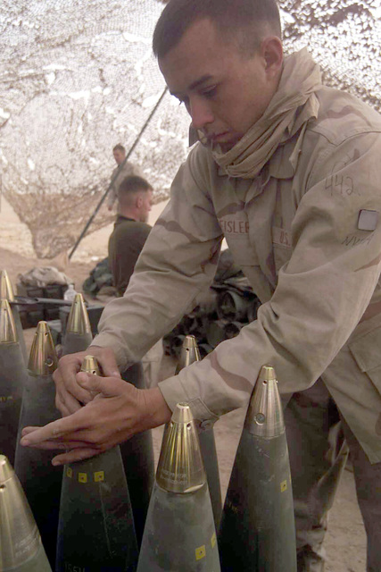 US Marine Corps (USMC) Corporal (CPL) Travis S. Geisler, a Cannonneer for Sierra Battery, Battalion Landing Team (BLT) 2/1, 15th Marine Expeditionary Unit Special Operations Capable (SOC), screw fuses onto the top of 155mm rounds in preparation for Operation IRAQI FREEDOM