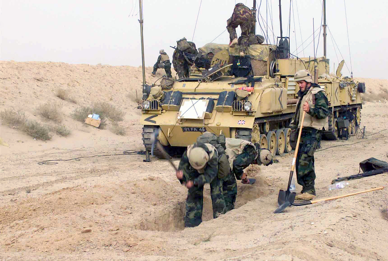 With a US Marine Corps (USMC) FV 430 Command Post Armored Personnel Carrier (APC) Vehicle in place behind him, Captain (CAPT) John Tinning, picks the rock hard ground as First Lieutenant (1LT) Jason Morrison, shovels the lose sand, while Corporal (CPL) Christopher Allen waits his turn, during Operation ENDURING FREEDOM