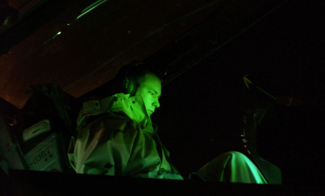 A US Air Force (USAF) crewchief assigned to the 410th Air Expeditionary Wing (AEW) tests avionics equipment on board an USAF F-16 Fighting Falcon preparing it for take off, during the opening minutes of A-Day, the commencement of the air war for Operation IRAQI FREEDOM, at a forward location