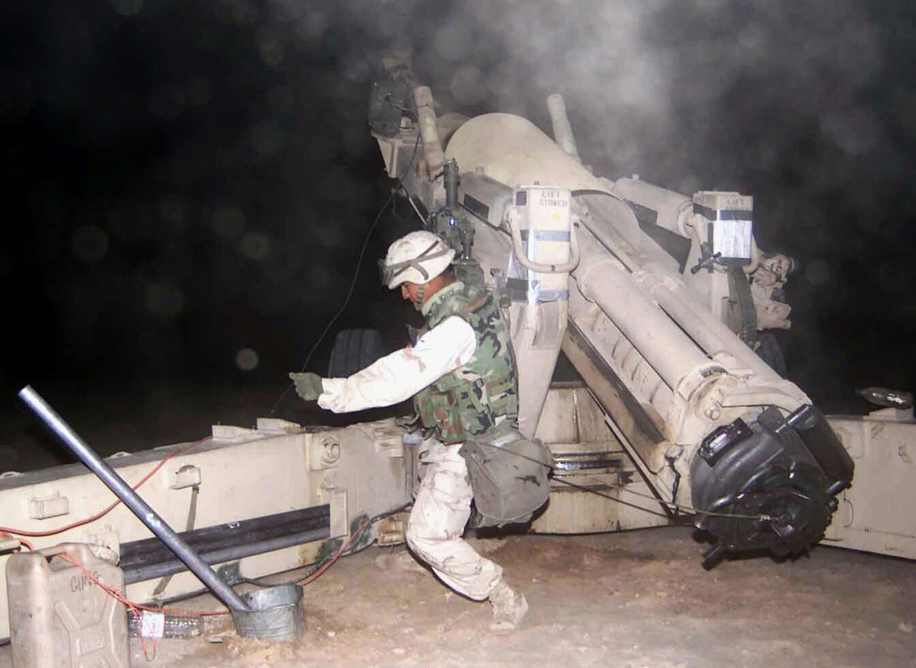 US Marine Corps (USMC) Lance Corporal (LCPL) Eder Dela Cruz, a Cannonneer for Sierra Battery, Battalion Landing Team (BLT) 2/1, 15th Marine Expeditionary Unit (MEU) Special Operations Capable (SOC), fires a 155mm round from an M198 Towed Howitzer using a lanyard, in support Operation IRAQI FREEDOM