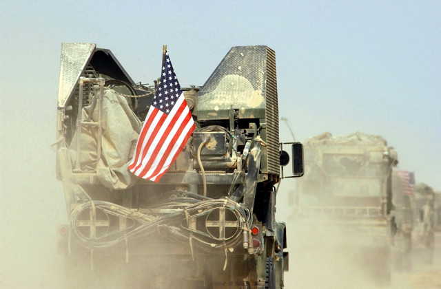 A convoy of US Military vehicles crosses the Iraqi border during the start of Operation IRAQI FREEDOM some military members showed their pride by flying the American Flag from their vehicle
