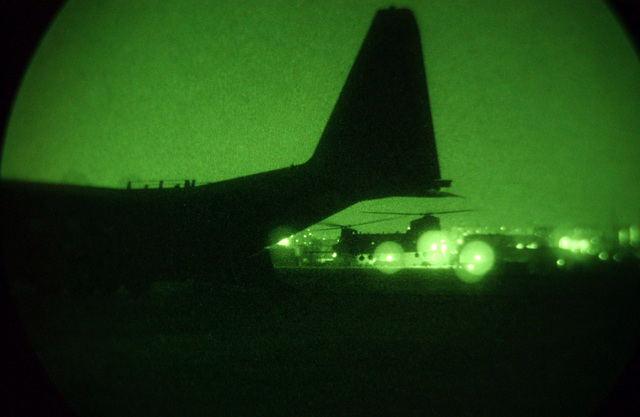 A nightscope view of night operations near a US Air Force (USAF) MC-130H Combat Talon II, 1ST Special Operation Squadron (SOS), Kadena Air Base (AB), Okinawa, as a US Army (USA) CH-47 Chinook, 160th Special Operations Air Regiment (SOAR) comes in for a landing at Tague AB, Korea. The nighttime operations are part of RECEPTION STAGING ONWARD MOVEMENT and INTEGRATION (RSO&I), and FOAL EAGLE which are joint and combined exercises for soldiers, sailors, airmen and Marines. They gather in Korea to work hand-in -hand with their South Korean counterparts for the purpose of showing the resolve of US forces to defend the Republic of Korea (ROK). It also gives the war fighters and planners an...