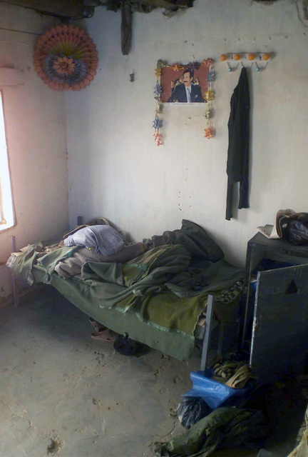 An Iraqi officer's bunk and quarters with a picture of Saddam Hussein on the wall, secured on patrol by the 7th Marine Regiment Combat Operations Center (COC), in support of Operation ENDURING FREEDOM