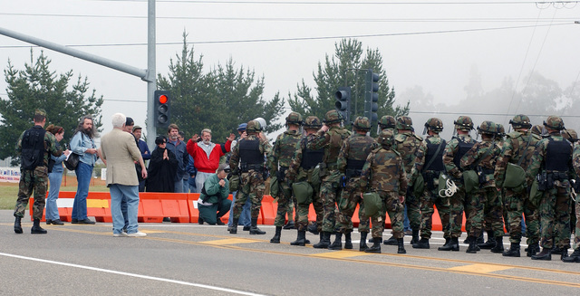 Protestors crowd the barrier lines at Vandenberg Air Force Base (AFB), California (CA), on March 22, 2003 as 30th Security Forces Squadron (SFS) members stand guard ready to apprehend any trespassers who come over the designated boundary