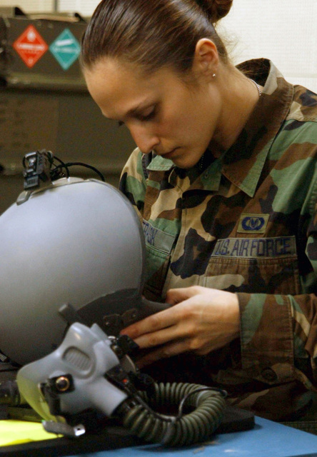 STAFF Sergeant Suzanne Trask with the 1ST Special Operation Squadron (1ST SOS), Kadena Air Base, Okinawa, Japan on March 22, 2003 inspects a flight helmet while on a TDY at Tague AB, Korea. SSgt Trask is taking part in RECEPTION STAGING ONWARD MOVEMENT and INTEGRATION (RSO&I), and FOAL EAGLE which are joint and combined exercises for soldiers, sailors, airmen and Marines to gather in Korea to work hand-in -hand with their South Korean counterparts for the purpose of showing the resolve of U.S. forces to defend the Republic of Korea (ROK) and to give the warfighters and planners an opportunity to operate in a joint (interservice) and combined (multinational) environment to safeguard the...