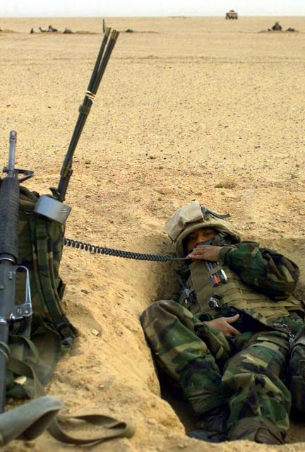 US Marine Corps (USMC) Corporal (CPL) Reinmar Maranon, Loader, Mike Battery, 3rd Battalion, 11th Marines (3/11), Twentynine Palms, California (CA), monitors the company radio from his fighting hole outside Az Zubayr during Operation IRAQI FREEDOM