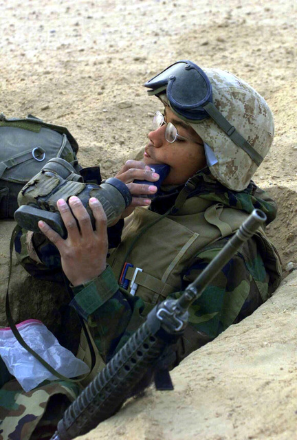 With his 5.56 mm M16A2 rifle and gas mask at his side, US Marine Corps (USMC) 2nd Lieutenant (2LT) Jair Vargas, Artillery Scout, Mike Battery, 3rd Battalion, 11th Marines (3/11), Twentynine Palms, California (CA), uses a pair of binoculars as a mirror to shave in his fighting hole outside Az Zubayr during Operation IRAQI FREEDOM