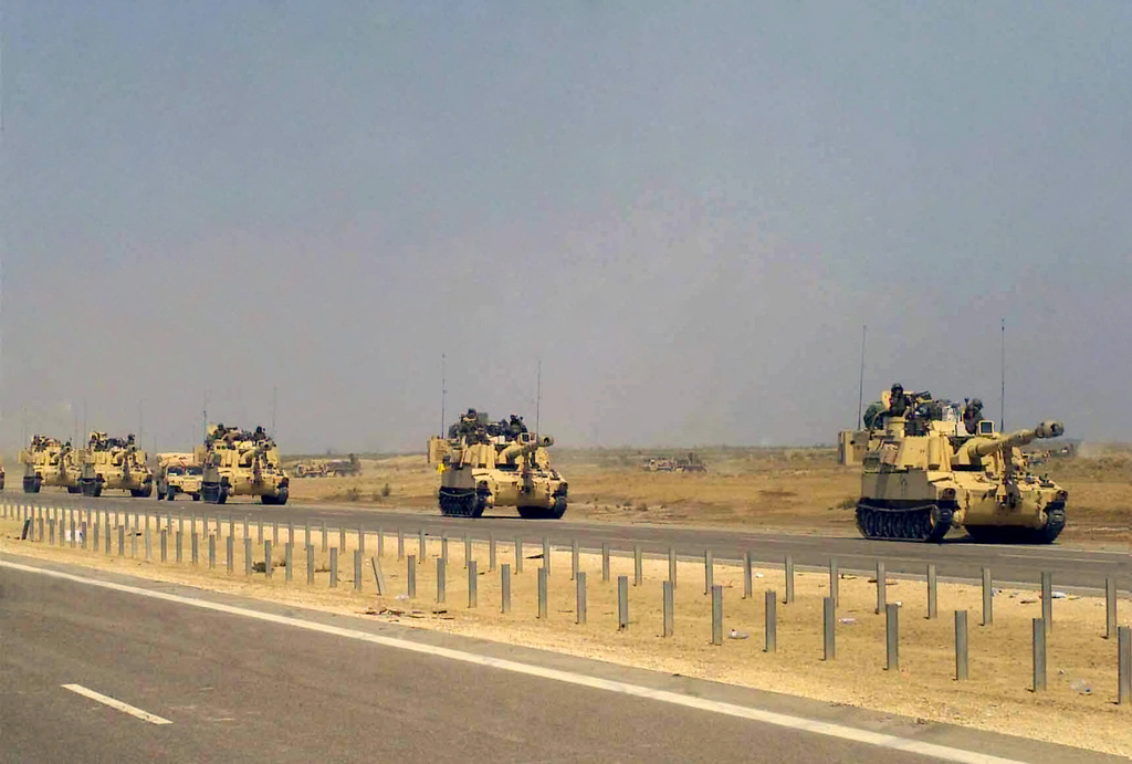 A convoy of US Army (USA) M109A6 155mm Paladin Self-propelled Howitzers travel along the highway on a march to the Euphrates River, in Iraq during Operation IRAQI FREEDOM