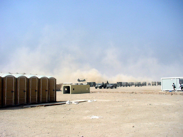 A view of the US Army (USA) Division Rear Theater of Operations Command Administrative Office (DREAR TOC AO) located at Udayri Range, Kuwait, during Operation IRAQI FREEDOM. A CH-47 Chinook helicopter creates a dust cloud as it lands in the background