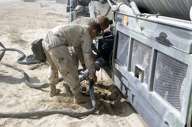 Private First Class (PFC) Matthew Rickman and Lance Corporal (LCPL) Brandon Fuhrman from Marine Wing Support Squadron (MWSS) 373rd, connect fuel hoses from a Marine refueling truck at a forward aircraft refueling point on Jalibah Air Base, Iraq, in support of Operation IRAQI FREEDOM