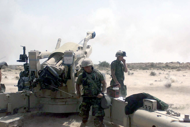 The ground shakes as a US Marine Corps (USMC) M198 155mm Towed Howitzer fires in support of Operation IRAQI FREEDOM