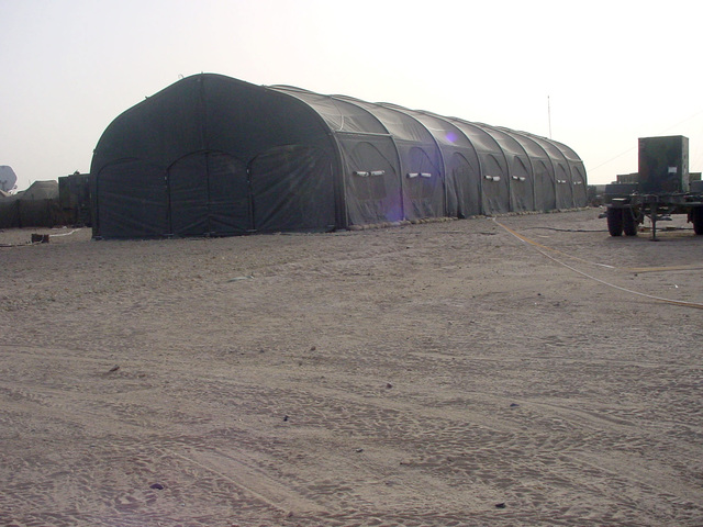 A 120x30-foot tent used by the US Army (USA) 101st Airborne Division Rear (DREAR) as the Theater of Operations Command (TOC) at Udayri Range in Kuwait, during Operation IRAQI FREEDOM. A portable 30-Kilowatt power supply generator is positioned foreground right