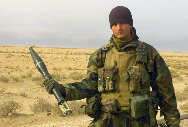 US Marine Corps (USMC) Corporal (CPL) Tyson Manker, assigned to Charlie Company, 1ST Battalion, 7th Marines, displays a PG-76 Anti Tank Grenade found in a weapons cache on the side of the highway near Az Zubayr, Iraq, during Operation IRAQI FREEDOM