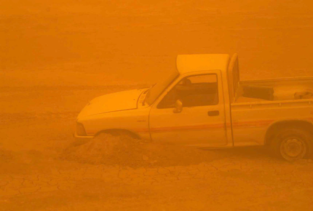 A partially destroyed Iraqi civilian truck, during a low visibility sandstorm, lay along the highway on a march to the Euphrates River, in Iraq during Operation IRAQI FREEDOM