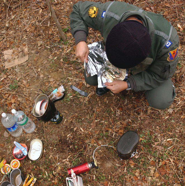 Republic of Korea Air Force (ROKAF) Captain (CAPT) Lee Jae Kyoung, 192nd Squadron, prepares breakfast during a Survival Evasion Resistance and Escape (SERE) scenario. SERE instructors are training ROKAF members how to navigate, communicate with, and guide USAF rescue units to their location during the Exercise FOAL EAGLE