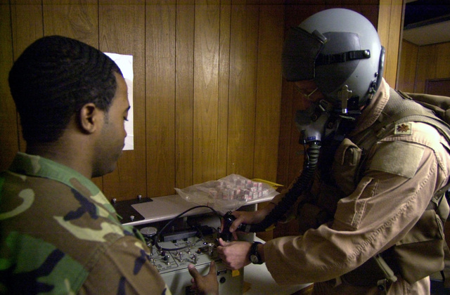 US Air Force (USAF) AIRMAN (AMN) Carter-Brown, Life Support, 457th Air Expeditionary Group (AEG), guides an aircrew member as they prepare to perform a fit mask test by checking for air leaks prior to bombing missions against Iraqi targets during Operation IRAQI FREEDOM