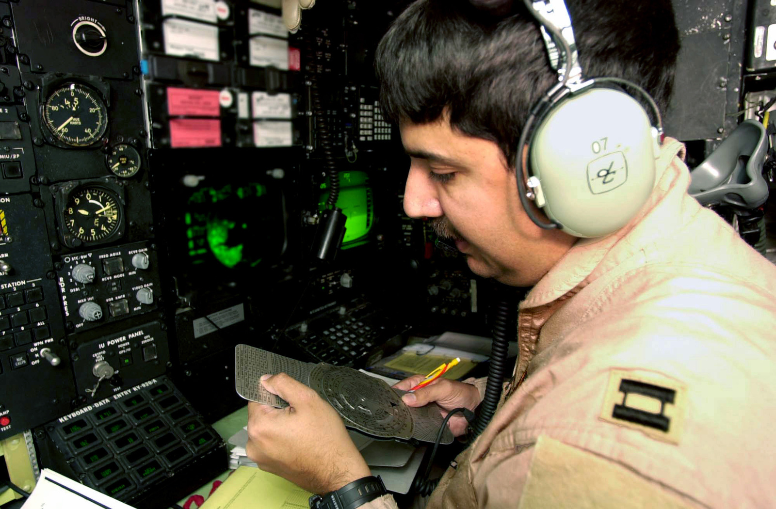 US Air Force (USAF) Captain (CAPT) Marc, Navigator, 23rd Expeditionary Bomb Squadron (EBS), Minot Air Force Base (AFB), North Dakota (ND), checks the flight plan with his E-6B Flight Computer at his station onboard the USAF B-52H Stratofortress bomber prior to a mission against Iraqi targets, during Operation IRAQI FREEDOM