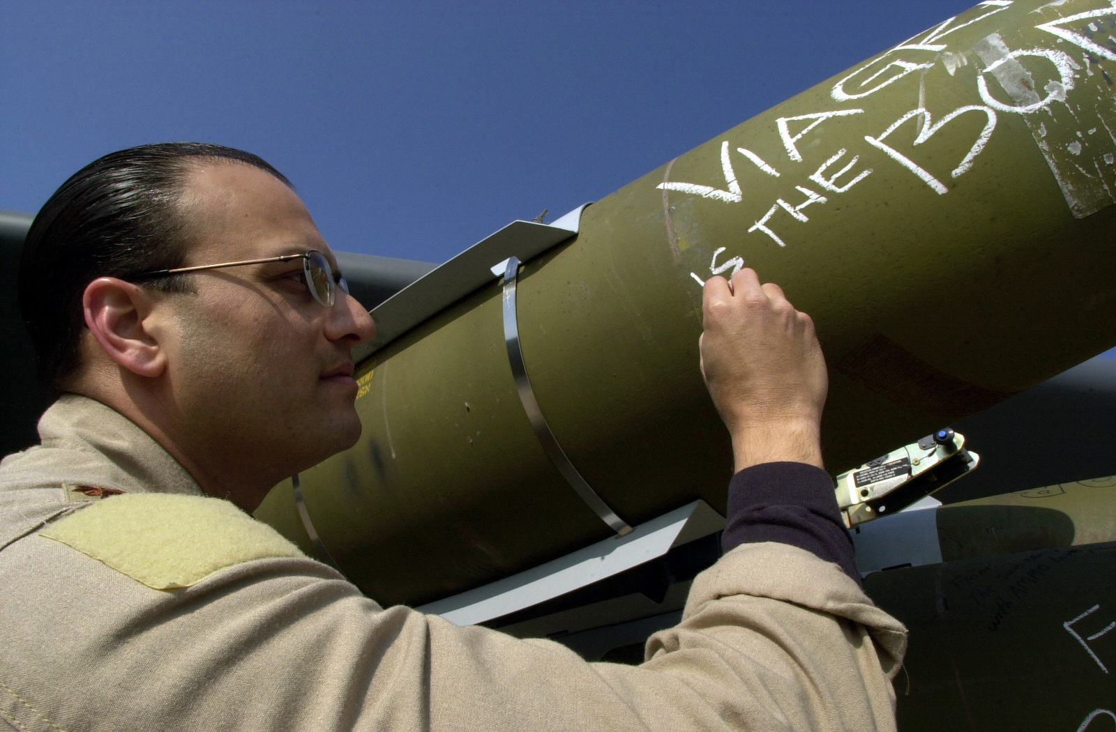 US Air Force (USAF) Major (MAJ) Roger, Radar Navigator, 23rd Expeditionary Bomb Squadron (EBS), Minot Air Force Base (AFB), North Dakota (ND), jots a final message on a JDAM (Joint Direct Attack Munitions) prior to the first ever B-52H Stratofortress bomber sortie with a configuration of Air-Launched Cruise Missile (ALCM) and JDAMs for military targets in Iraq during Operation IRAQI FREEDOM
