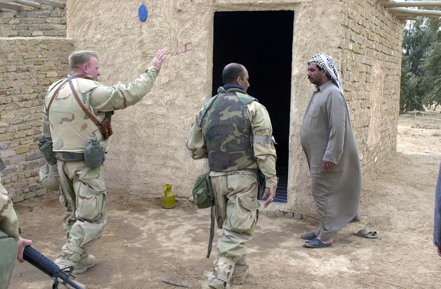 US Army (USA) Lieutenant Colonel (LTC) Alan King (left), 422nd Civil Affairs Battalion, greets and Iraqi homeowner in central Iraq, as he and other coalition forces soldier check on the water quality at a nearby reservoir. USA and Coalition Forces are in Iraq in support of Operation IRAQI FREEDOM