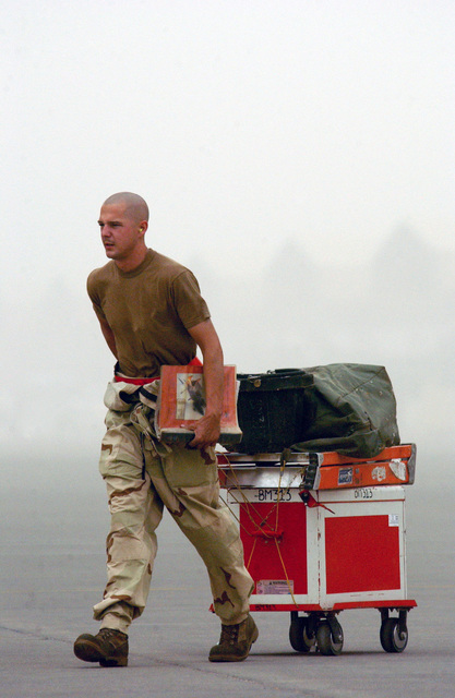 US Air Force (USAF) SENIOR AIRMAN (SRA) Aaron Watts, Crewchief, 67th Aircraft Maintenance Unit (AMU) deployed to the 363rd Expeditionary Maintenance Squadron (EMXS), prepares for a shift change in the mist of a sandstorm during Operation IRAQI FREEDOM. Operation IRAQI FREEDOM is the multi-national coalition effort to liberate the Iraqi people, eliminate Iraqs weapons of mass destruction and the regime of Saddam Hussein
