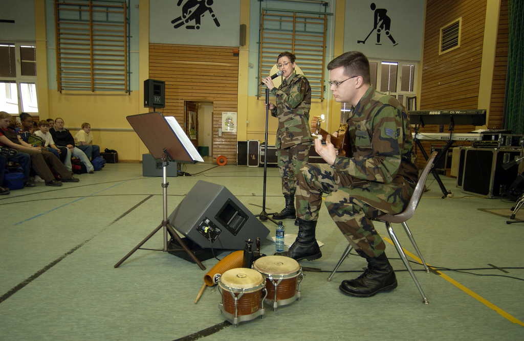 """US Air Force (USAF) STAFF Sergeant (SSGT) Donna Siler, vocalist, and USAF SENIOR AIRMAN (SRA) Toby McWilliams, Guitarist, United States Air Forces in Europe (USAFE) Band """"Galaxy,"""" perform during """"Music in our Schools"""" month at Landstuhl Middle School. Galaxy performs rock and contemporary music throughout Europe as part of the USAFE Band"""