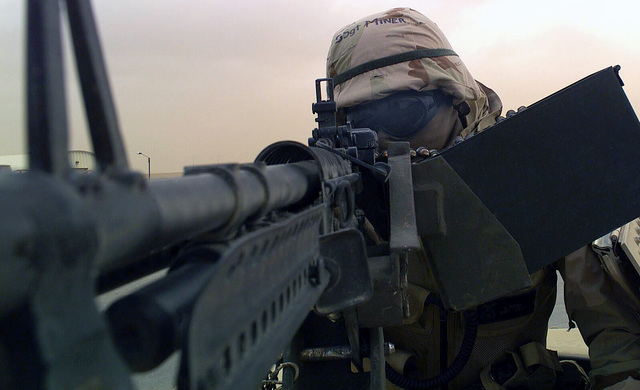 US Air Force (USAF) STAFF Sergeant (SSGT) Miner, 410th Expeditionary Security Forces Squadron (ESPS), 410th Air Expeditionary Wing (AEW), keeps a vigilant eye over the front gate during a heavy sandstorm with a Saco 7.62 mm M60 general purpose machine gun at a forward undisclosed location during Operation IRAQI FREEDOM. Operation IRAQI FREEDOM, the multi-national coalition effort to liberate the Iraqi people and eliminate, Iraqi's weapons of mass destruction and end the regime of Saddam Hussein
