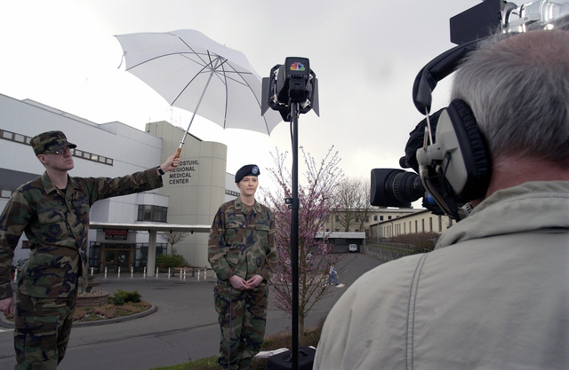 US Army (USA) Lieutenant Colonel (LTC) Susan Raymond, Head Intensive Care Unit Nurse, Landstuhl Regional Medical Center, Germany, speaks live via satellite with the NBC Today Show, on the current condition of patients that sustained wounds during Operation IRAQI FREEDOM. US Air Force (USAF) Second Lieutenant (2LT) Bates holds an umbrella to shield equipment from the light rain