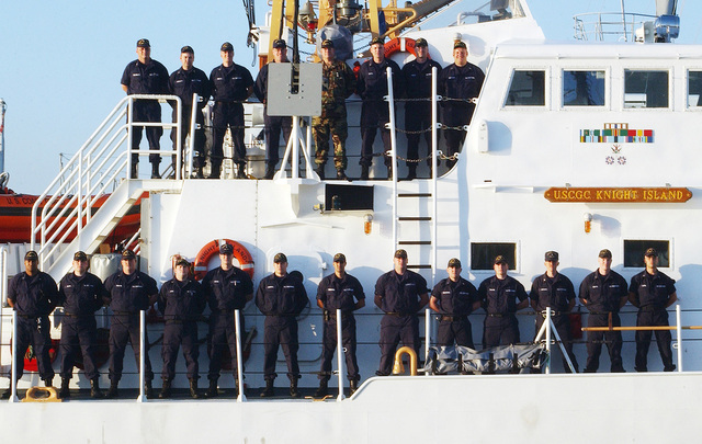 US Coast Guard (USCG) Sailors man the rails of the USCG ISLAND CLASS: Patrol Craft, KNIGHT ISLAND (WPB 1348), as the Ships company welcomes the Commodore of Naval Costal Warfare Group Two onboard to celebrate his twenty-fifth year of commission and naval service