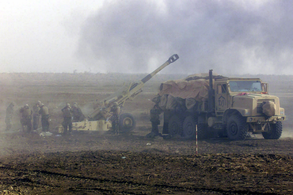 US Marine Corps (USMC) Marine assigned to I/Battery, 3rd Battalion, 5th Marines, 1ST Marine Division, fire their M198 155mm Howitzers against enemy targets in Iraq. An USMC M923 5-ton (6x6) truck is park to the right. USMC personnel are in Iraq in support of Operation IRAQI FREEDOM