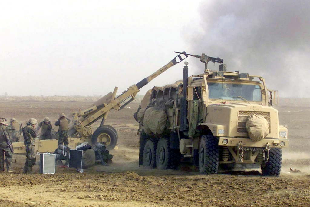 US Marine Corps (USMC) with India Battery, 3rd Battalion, 5th Marines, 1ST Marine Division out of Camp Pendleton, California, fire their in-line M198 155mm Medium Towed Howitzer artillery against possible enemy contact in Iraq, while an MK-23 Medium Tactical Vehicle Replacement (MTVR) cargo truck delivers ammunition, during the early phase of Operation IRAQI FREEDOM