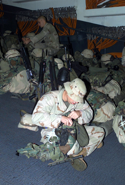 US Marine Corps (USMC) Corporal (CPL) Bryan M. Acuff, a rifleman assigned to 2nd Platoon, F/Company, Battalion Landing Team, 2nd Battalion, 2nd Marines, 24th Marine Expeditionary Unit (MEU), Special Operations Capable (SOC), checks over his 782 gear (deployment gear) inside the well deck aboard the US Navy (USN) WASP CLASS: Amphibious Assault Ship, USS NASSAU (LAH 4), enroute to participate in Operation IRAQI FREEDOM