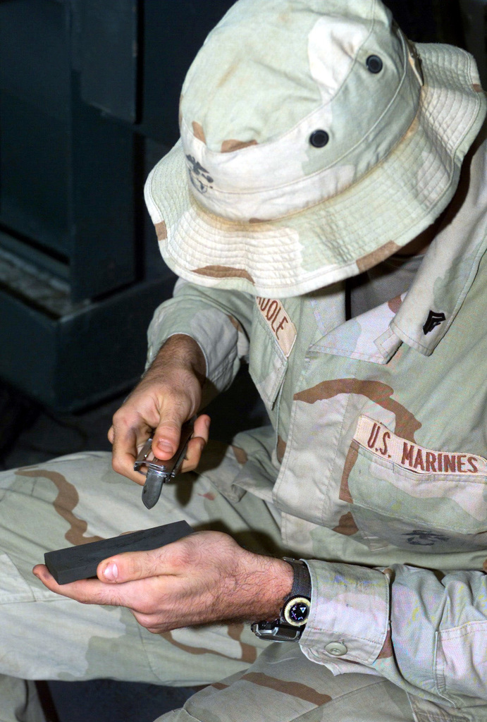 US Marine Corps (USMC) Corporal (CPL) Scott T. Madole, a fire team leader assigned to, Fox/Company, 2nd Platoon, Battalion Landing Team, 2nd Battalion, 2nd Marines, 24th Marine Expeditionary Unit (MEU), Special Operations Capable (SOC), uses a stone to sharpen his pocket knife, inside the well deck aboard the US Navy (USN) WASP CLASS: Amphibious Assault Ship, USS NASSAU (LAH 4), enroute to participate in Operation IRAQI FREEDOM