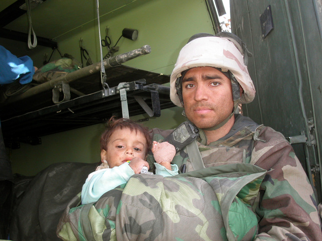 US Navy (USN) Hospital Corpsman 3rd Class (HM3) Peacher, assigned to Regimental Combat Team One (RCT-1), comforts a displaced Iraqi child after rendering medical attention to the infant who was hurt during fighting near Al Shatra, Iraq, during Operation IRAQI FREEDOM